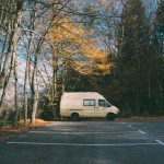 Car park that was lay by tarmac contractors bordered with trees and a van parked in a space